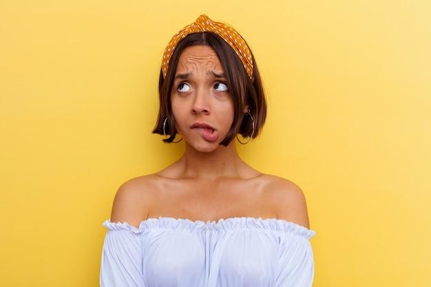 Mujer joven de raza mixta aislada sobre fondo amarillo confundida, se siente dudosa e insegura.