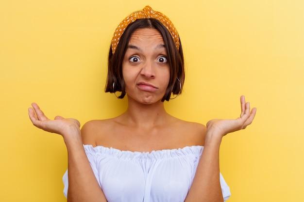 Mujer joven de raza mixta aislada sobre fondo amarillo dudando y encogiéndose de hombros en gesto de interrogación.