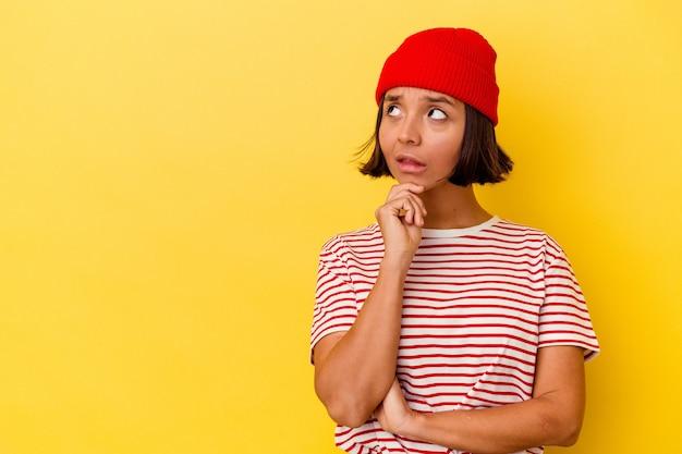 Mujer joven de raza mixta aislada sobre fondo amarillo mirando hacia los lados con expresión dudosa y escéptica.