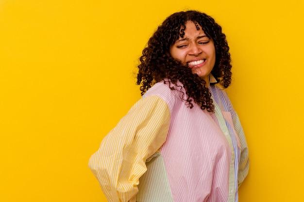 Mujer joven de raza mixta aislada sobre fondo amarillo que sufre un dolor de espalda.