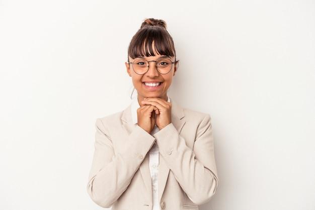 Mujer joven de raza mixta aislada sobre fondo blanco mantiene las manos bajo la barbilla, está mirando felizmente a un lado.