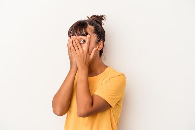 Mujer joven de raza mixta aislada sobre fondo blanco parpadear a través de los dedos asustada y nerviosa.