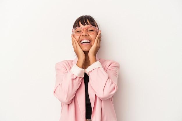Mujer joven de raza mixta aislada sobre fondo blanco se ríe con alegría manteniendo las manos en la cabeza. concepto de felicidad.