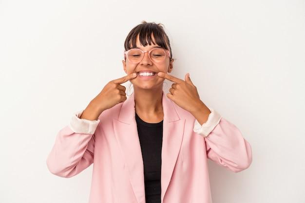 Mujer joven de raza mixta aislada sobre fondo blanco sonríe, señalando con el dedo a la boca.
