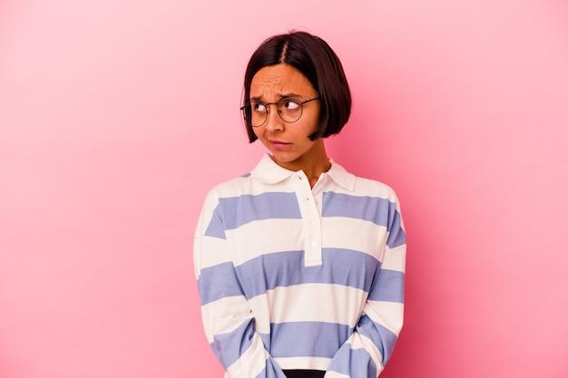 Mujer joven de raza mixta aislada sobre fondo rosa confundida, se siente dudosa e insegura.