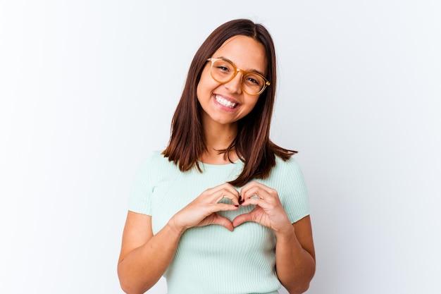 Mujer joven de raza mixta aislada sonriendo y mostrando una forma de corazón con las manos.