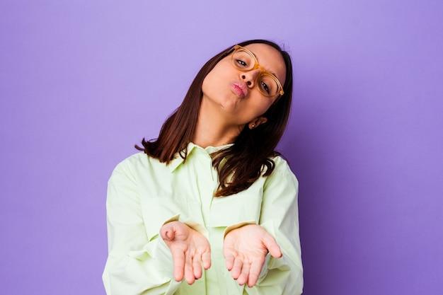 Mujer joven de raza mixta aisló los labios plegables y sosteniendo las palmas para enviar beso de aire.