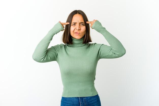 Mujer joven de raza mixta se centró en una tarea, manteniendo los dedos índices apuntando con la cabeza.