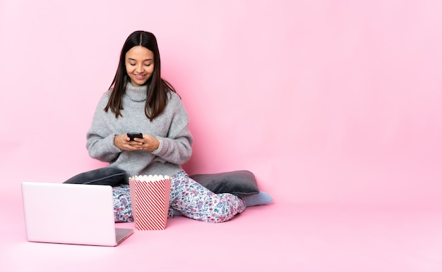 Mujer joven de raza mixta comiendo palomitas de maíz mientras ve una película en la computadora portátil enviando un mensaje con el móvil
