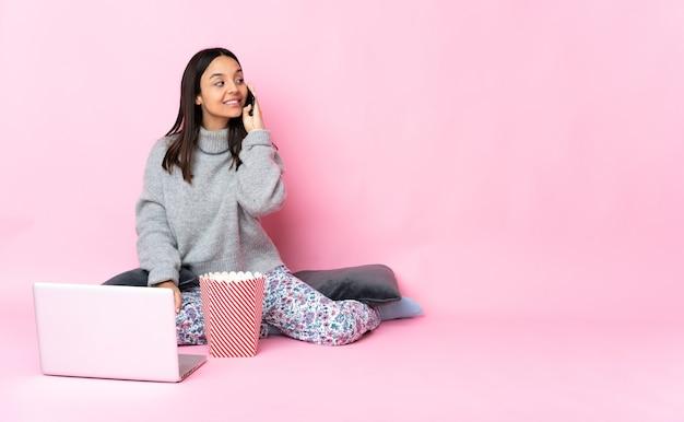 Mujer joven de raza mixta comiendo palomitas de maíz mientras ve una película en la computadora portátil manteniendo una conversación con el teléfono móvil con alguien