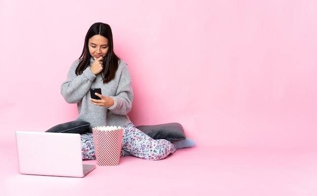 Mujer joven de raza mixta comiendo palomitas de maíz mientras ve una película en la computadora portátil pensando y enviando un mensaje