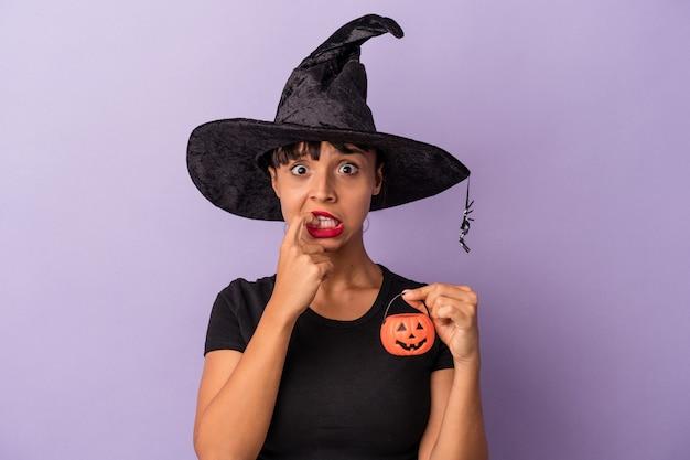 Mujer joven de raza mixta disfrazada de bruja aislada sobre fondo púrpura mordiéndose las uñas, nerviosa y muy ansiosa.