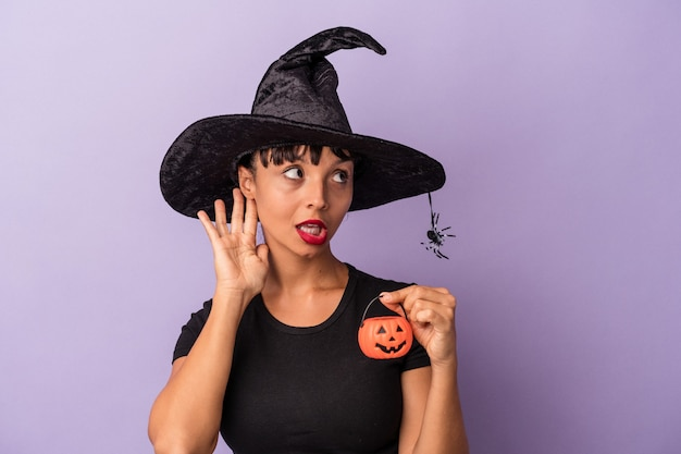 Mujer joven de raza mixta disfrazada de bruja aislada sobre fondo púrpura tratando de escuchar un chisme.
