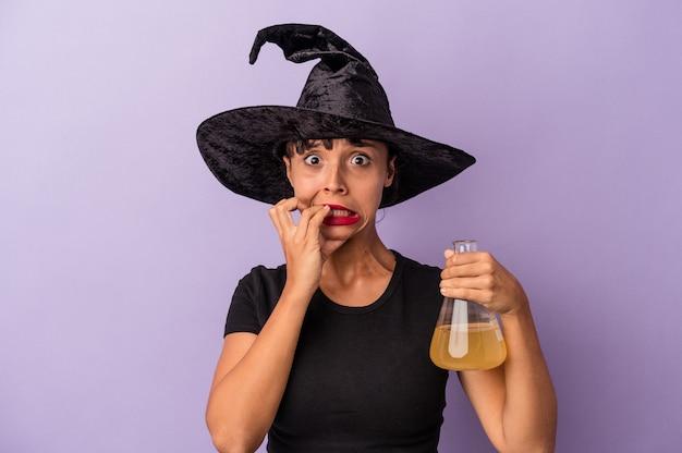 Mujer joven de raza mixta disfrazada de bruja con poción aislada sobre fondo púrpura mordiéndose las uñas, nerviosa y muy ansiosa.