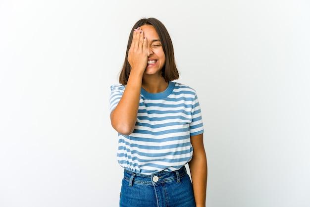 Mujer joven de raza mixta divirtiéndose cubriendo la mitad de la cara con la palma.