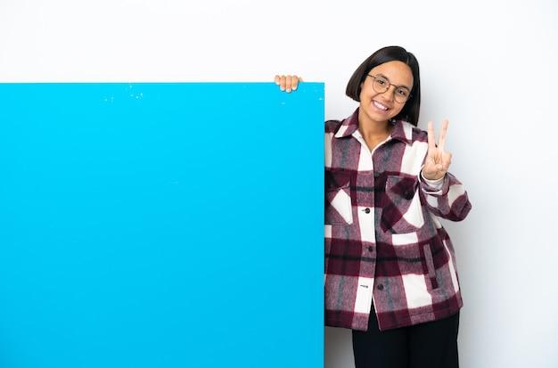 Mujer joven de raza mixta con un gran cartel azul aislado sonriendo y mostrando el signo de la victoria