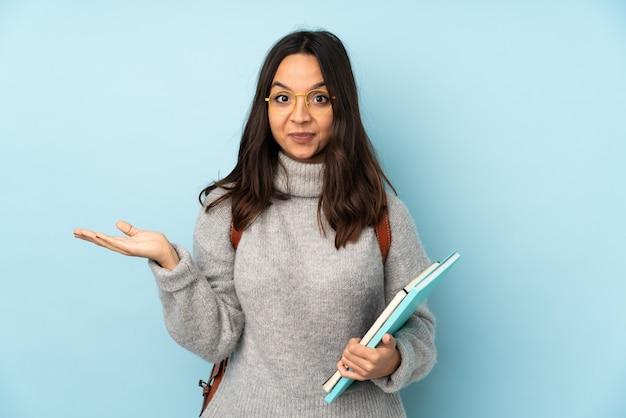 Mujer joven de raza mixta que va a la escuela en la pared azul que tiene dudas mientras levanta las manos