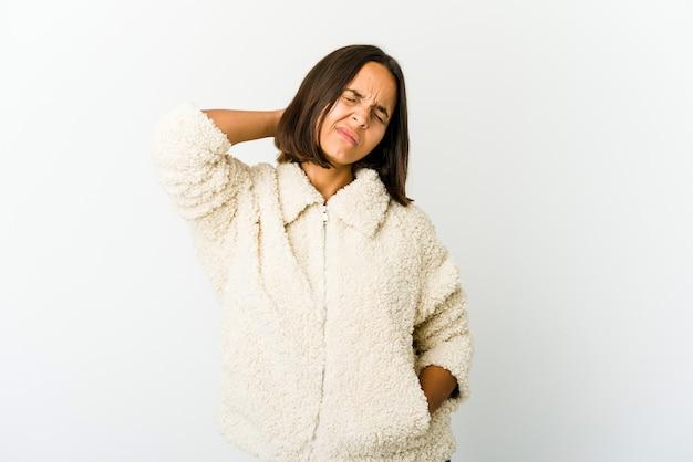 Mujer joven de raza mixta que tiene dolor de cuello debido al estrés, masajeando y tocándolo con la mano.