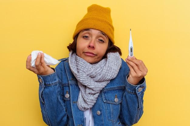 Mujer joven de raza mixta con un resfriado sobre fondo amarillo