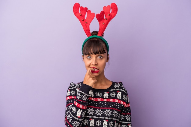 Mujer joven de raza mixta con sombrero de reno celebrando la navidad aislado sobre fondo púrpura mordiéndose las uñas, nervioso y muy ansioso.