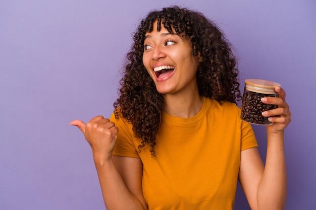 Mujer joven de raza mixta sosteniendo una botella de granos de café aislada en puntos de fondo púrpura con el dedo pulgar, riendo y despreocupado.
