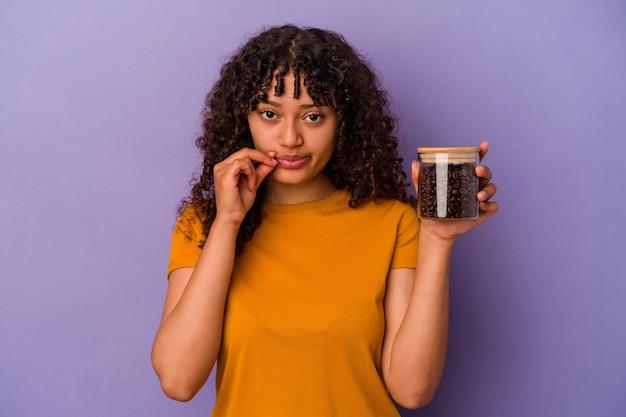 Mujer joven de raza mixta sosteniendo una botella de granos de café aislada sobre fondo púrpura con los dedos en los labios guardando un secreto.