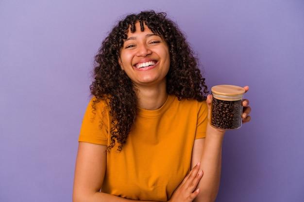 Mujer joven de raza mixta sosteniendo una botella de granos de café aislada sobre fondo púrpura riendo y divirtiéndose.