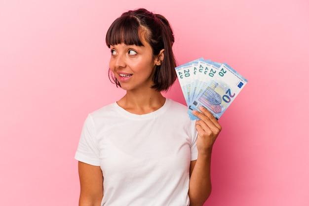 Mujer joven de raza mixta sosteniendo facturas aisladas sobre fondo rosa se ve a un lado sonriente, alegre y agradable.