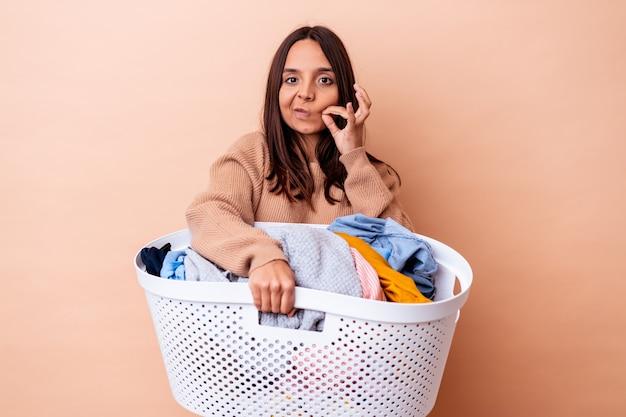 Mujer joven de raza mixta sosteniendo una lavandería aislada con los dedos en los labios guardando un secreto.