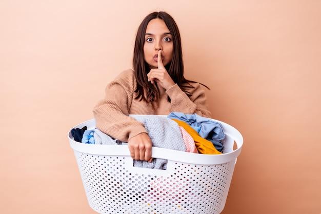 Mujer joven de raza mixta sosteniendo una lavandería aislada manteniendo un secreto o pidiendo silencio.