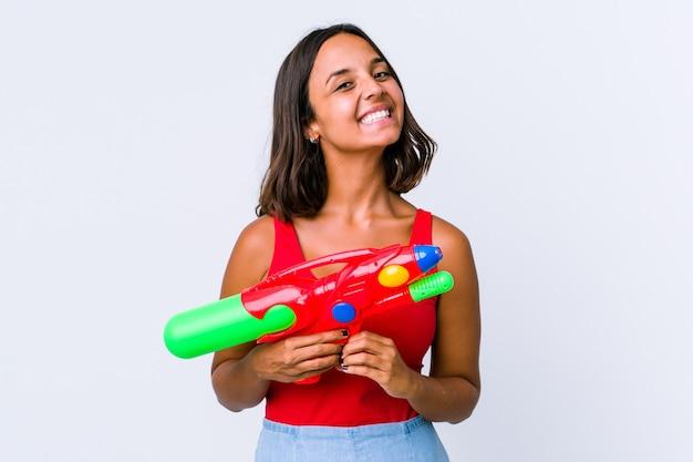 Mujer joven de raza mixta sosteniendo una pistola de agua aislada sonriendo y mostrando una forma de corazón con las manos.