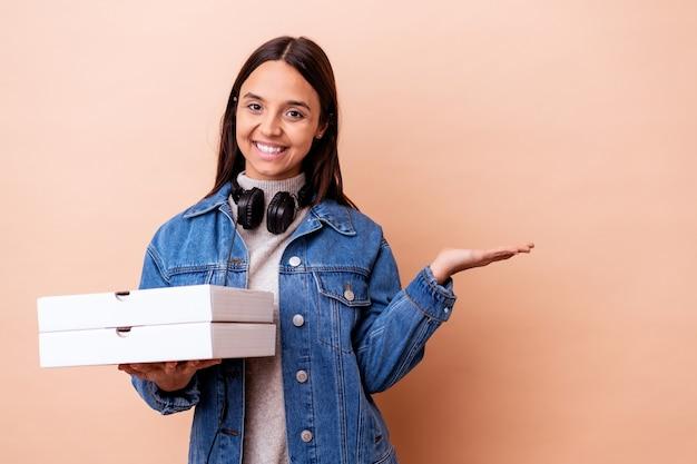 Mujer joven de raza mixta sosteniendo una pizza aislada mostrando un espacio de copia en una palma y sosteniendo otra mano en la cintura.