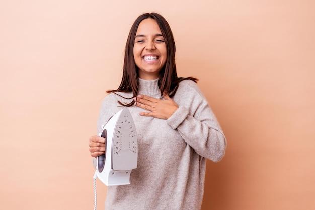 Mujer joven de raza mixta sosteniendo una plancha aislada se ríe a carcajadas manteniendo la mano en el pecho.