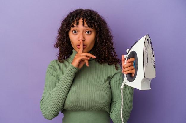 Mujer joven de raza mixta sosteniendo una plancha aislada sobre fondo púrpura manteniendo un secreto o pidiendo silencio.