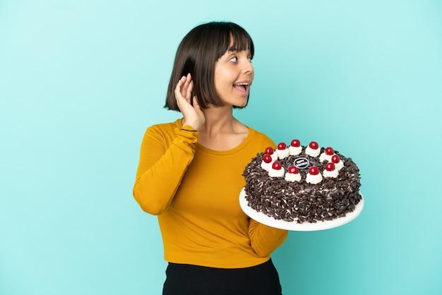 Mujer joven de raza mixta sosteniendo la torta de cumpleaños escuchando algo poniendo la mano en la oreja