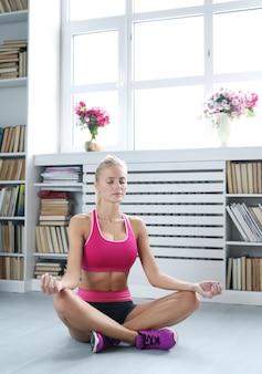 Mujer joven realiza movimientos de yoga en casa