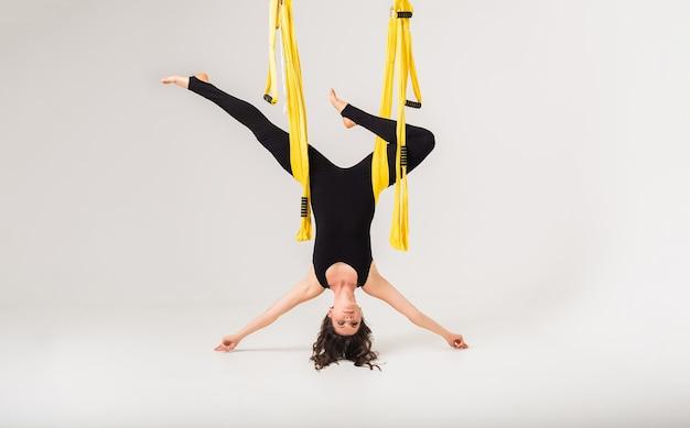 Una mujer joven realiza una pose de yoga invertida en una hamaca amarilla sobre un fondo blanco aislado con una copia del espacio