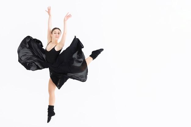 Mujer joven realizando danza con espacio de copia