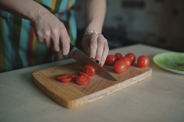 Mujer joven, rebanar, tomates