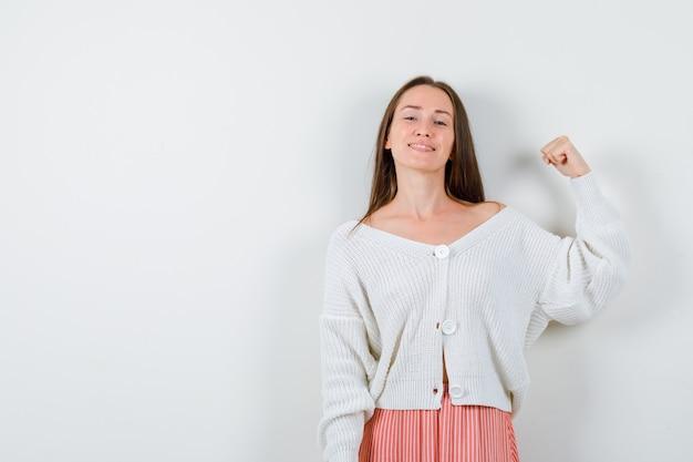 Mujer joven en rebeca y falda mostrando gesto de ganador mirando feliz aislado