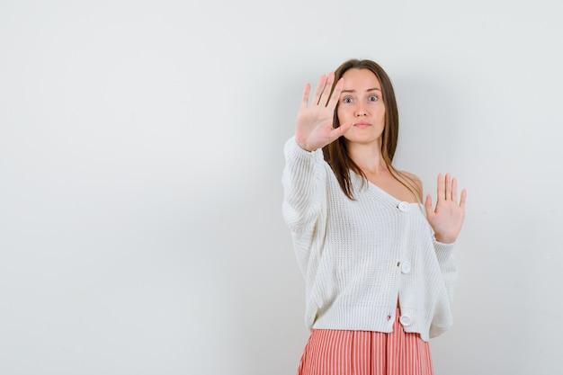 Mujer joven en rebeca y falda mostrando gesto de parada mirando asustado aislado