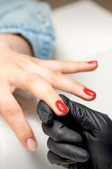 Mujer joven recibe esmalte de uñas rojo por maestro de manicura profesional en salón de uñas