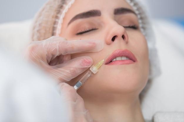 Mujer joven recibe inyecciones faciales de belleza en el salón