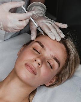 Mujer joven recibiendo una inyección de belleza