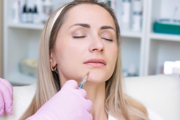 Mujer joven recibiendo inyección cosmética. mujer en un salon de belleza