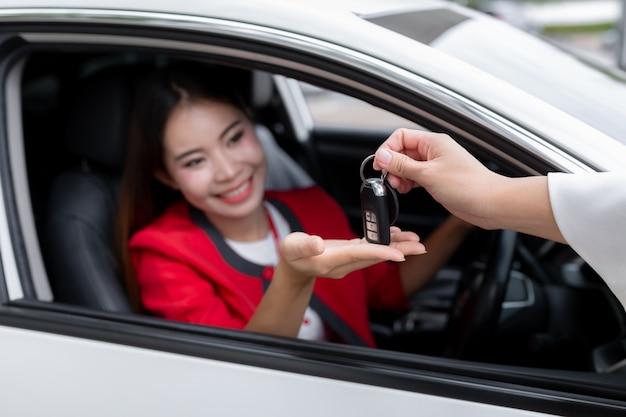 Mujer joven recibiendo las llaves de su nuevo carro.