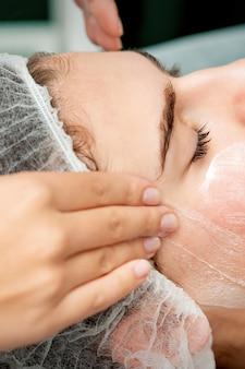 Mujer joven recibiendo masaje facial con los ojos cerrados por esteticista en salón de belleza