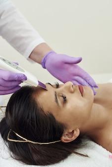 Mujer joven recibiendo terapia de limpieza con un equipo de ultrasonidos profesional