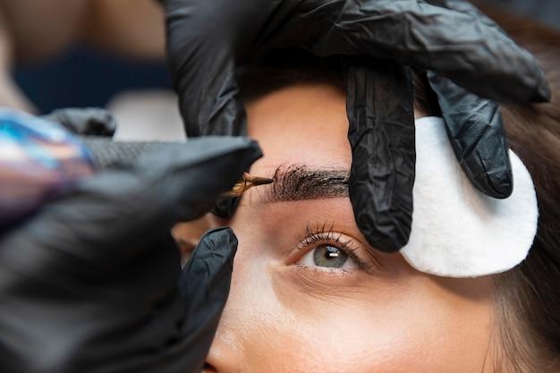 Mujer joven recibiendo un tratamiento de belleza para sus cejas