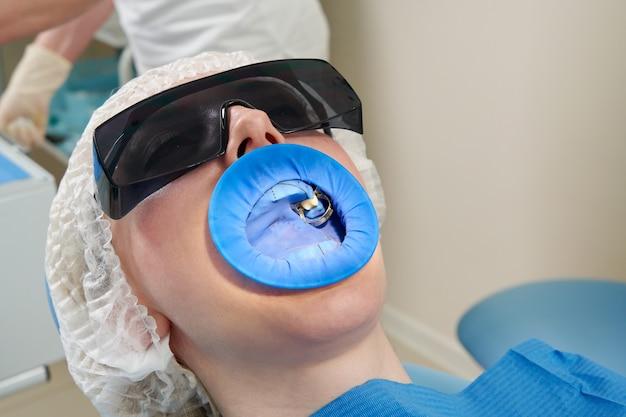 Mujer joven recibiendo tratamiento dental en el consultorio del dentista con una protección de dique de goma dental